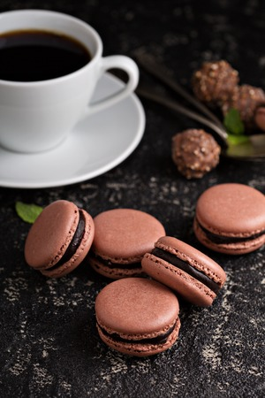 Chocolate french macarons with ganache filling on a black table with coffee