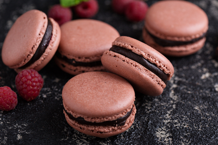ganache: Chocolate and raspberry french macarons with ganache filling on a black table
