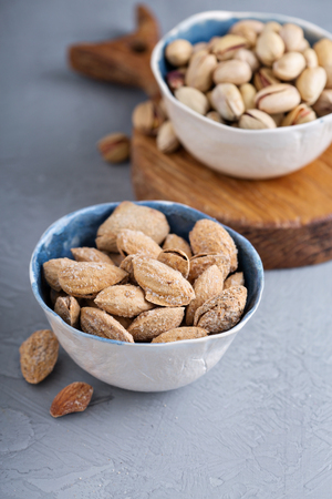 pista: Salted almonds and pistachios in a shell on gray background