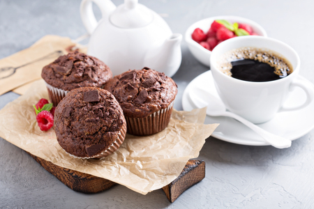Chocolate muffins with a cup of coffee and fresh berries on the table Stock Photo - 60719691