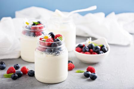 Yogourt frais fait maison dans de petits pots servis avec des baies fraîches