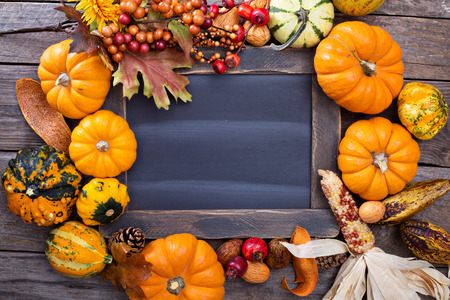 Variety of colorful decorative pumpkins around a chalkboard with copy space Stock Photo