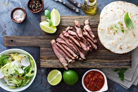 얇게 썬 회의 및 커팅 보드에 tortillas와 스테이크 타코 요리