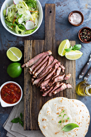 gallo: Cooking steak tacos with sliced meet and tortillas on a cutting board