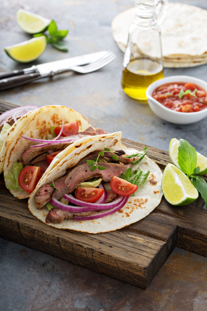 gallo: Steak tacos with sliced meet, salad and tomato salsa on a cutting board