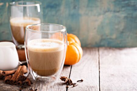 Pumpkin latte in glasses on a wooden table - fall coffee drink