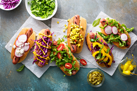 condiments: Variety of hot dogs with healthy vegetable garnishes and condiments