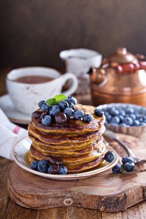 butternut: Pumpkin pancakes in high stack with blueberries and syrup served with tea in a rustic setting