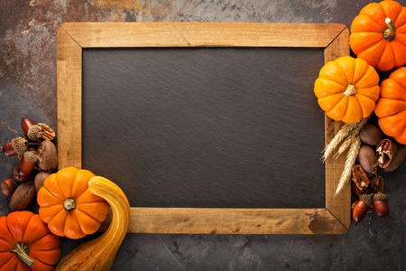Fall chalkboard frame background with pumpkins and nuts