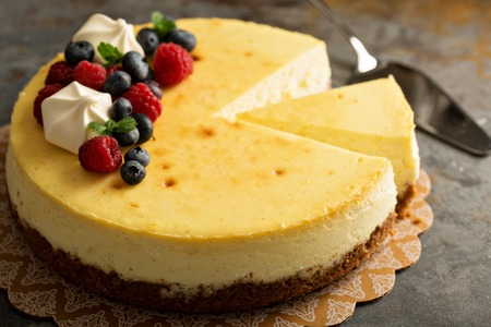Homemade New York cheesecake on a cake stand decorated with fresh berries Standard-Bild
