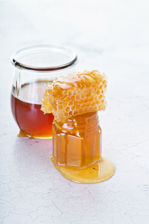 Jar of honey and honeycomb on distressed white background Stock Photo