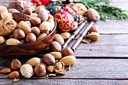 Variety of nuts with shells with Christmas decorations, holiday still life