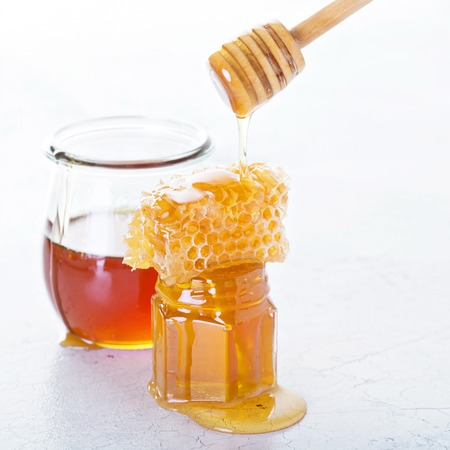 Jar of honey and honeycomb on distressed white background Reklamní fotografie