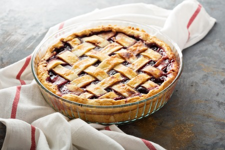 Homemade cherry pie with lattice on a distressed background Stock Photo