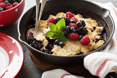 Berry crumble in a cast iron pan with fresh raspberry and blueberry Stock Photo