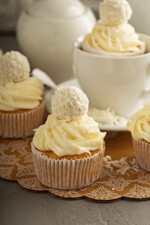 Coconut cupcakes with white frosting decorated with candy 스톡 콘텐츠