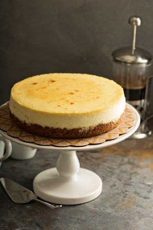 Homemade New York cheesecake on a cake stand decorated with fresh berries Foto de archivo