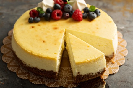 Tarta de queso casera de Nueva York en un soporte de pastel decorado con bayas frescas