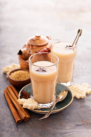 Hot masala chai, tea with spices and brown sugar Фото со стока