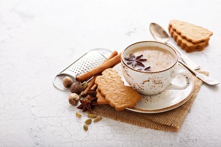 Masala-thee in keramische kop met kruiden en peperkoekkoekjes Stockfoto