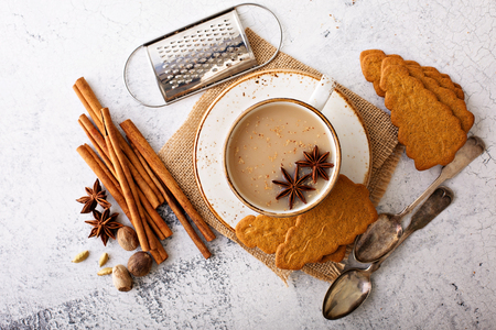 Masala tea in ceramic cup with winter spices and gingerbread cookies