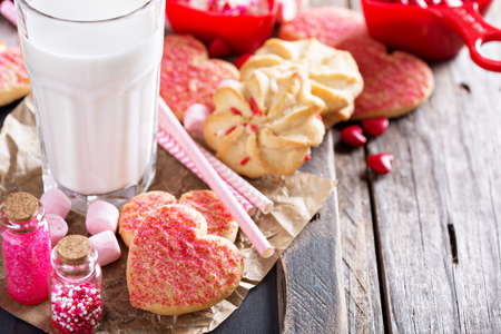 Valentines day cookies decorated with sprinkles and a glass of milk