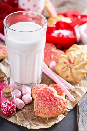Valentine's day cookies decorated with sprinkles and a glass of milk 免版税图像 - 122038379