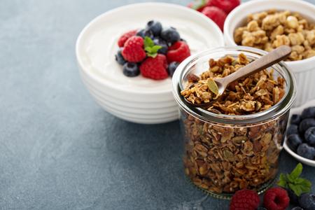Homemade granola in glass jar with yogurt and fresh berries
