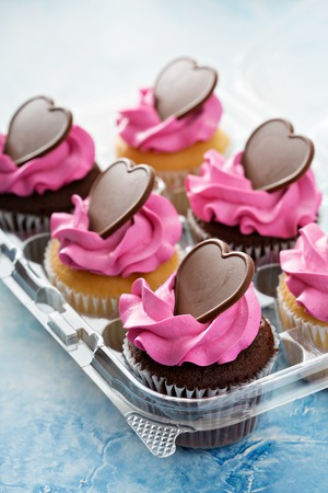 Romantic cupcakes with pink frosting and chocolate hearts