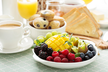 Fresh and bright continental breakfast table with coffee, muffins and fruits Stock Photo