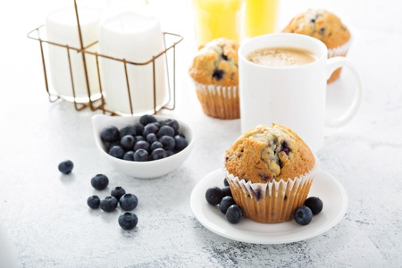 breakfast with blueberry muffin, big cup of coffee and milk in bottles Standard-Bild