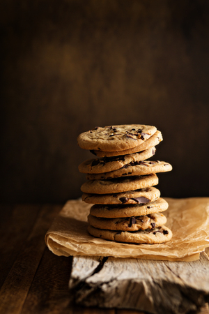 Homemade chocolate chip cookies stacked in a rusting setting