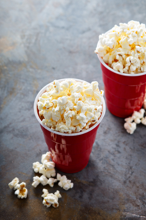 Tasty salted traditional popcorn in red plastic cups
