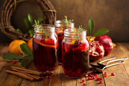 Pomegranate and orange winter or autumn cocktail, punch or sangria in mason jar