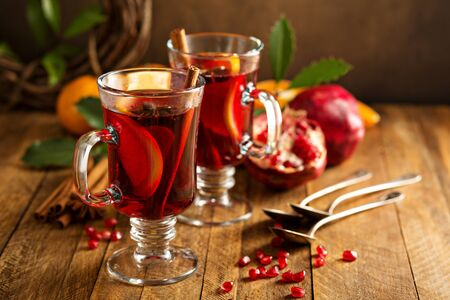Mulled wine with pomegranate and orange in a rustic setting Stock Photo
