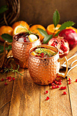 Christmas Moscow mule with pomegranate and orange in a rustic setting