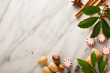 Holiday background with peppermint candy, nuts and spices on marble