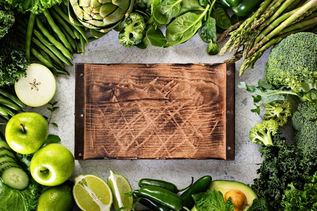 Variety of green vegetables and fruits copyspace with cutting board on white