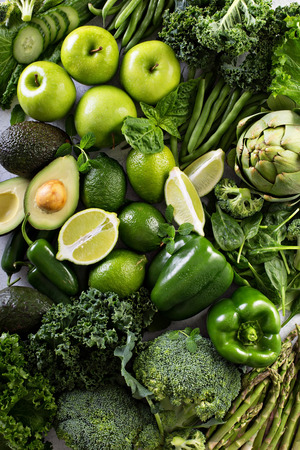 Variety of green vegetables and fruits spread on the table