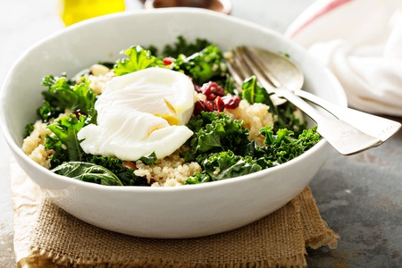 Healthy raw kale and quinoa salad with poached egg on top Stok Fotoğraf