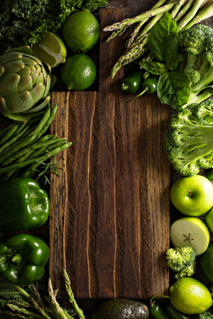 Variety of green vegetables and fruits copyspace with cutting board