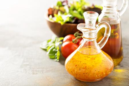 Italian vinaigrette dressing in a vintage bottle with fresh vegetables on the table 스톡 콘텐츠