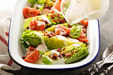 Wedge salad with baby lettuce, cherry tomatoes, bacon and ranch dressing pouring over