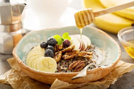 Quinoa porridge with banana, blueberry and pecan nuts for breakfast Stock Photo
