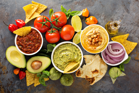 Homemade hummus, salsa and guacamole with corn chips and vegetables overhead view