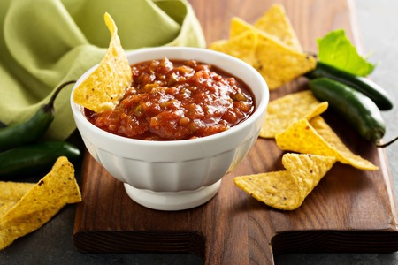 Red tomato spicy salsa with corn chips