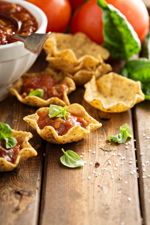 Small mexican style appetizers made with tortilla bowls and tomato salsa