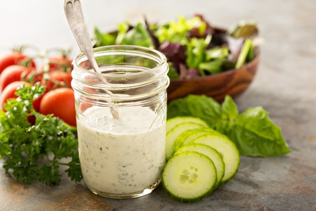 Homemade ranch dressing in a mason jar with fresh vegetables 스톡 콘텐츠