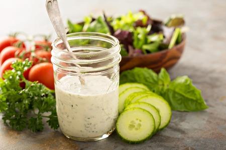 Homemade ranch dressing in a mason jar with fresh vegetables Standard-Bild