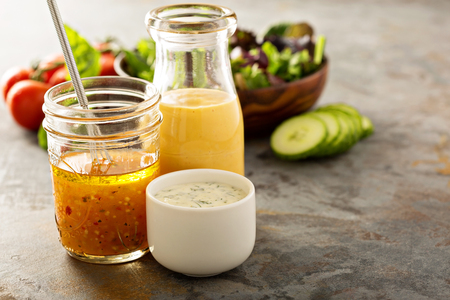 Variety of homemade sauces and salad dressings in jars including vinaigrette, ranch and honey mustard